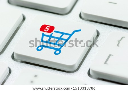 Online shopping / ecommerce and retail sale concept : Shopping cart with 5 items in a basket, a trolley symbol on a laptop keyboard, depicts customers order things from retailer sites using internet