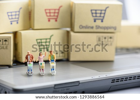 Online shopping / ecommerce concept : Miniature figurine shoppers push a shopping cart on a computer laptop, depicts buyers or consumers order or buy things from retailer stores over the internet site