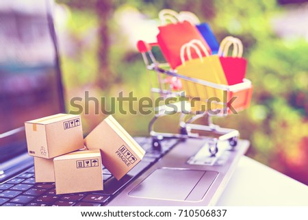 Online shopping, electronic commerce or ecommerce concept : Crystal clear globe etched with world map on a white computer keyboard and a shopping cart icon or symbol with a phrase Online Shopping. #710506837