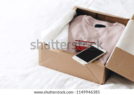 Online shopping fashion items opening box by using smartphone and credit card on a white background with copy space #1149946385