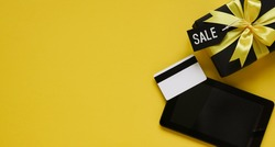 Online shopping for Black Friday and Christmas sales,pay by credit card.Black gift box with yellow bow,tablet,black tags,credit card on yellow background,top view,flat lay,copy space,close-up.