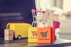Online shopping, logistics, supply chain and shipment service, e-commerce concept : Paper bags, boxes of goods, trolley, delivery van on a laptop, depicts customers uses internet to order / buy things