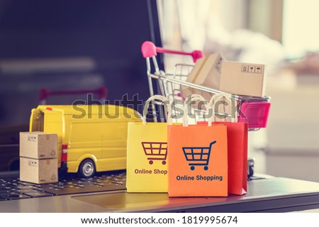 Online shopping, logistics, supply chain and shipment service, e-commerce concept : Paper bags, boxes of goods, trolley, delivery van on a laptop, depicts customers uses internet to order  buy things