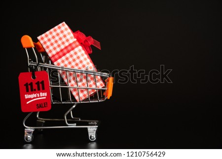 Online shopping of China, 11.11 single day sale concept. Red ticket 11.11 single day sale tag hanging on shopping bag with gift boxes.