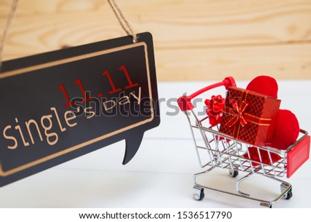 Online shopping of China, 11.11 single's day sale concept. The red shopping cart, red ribbon and red heart pillow on white and brown background with copy space for text 11.11 single's day sale.
