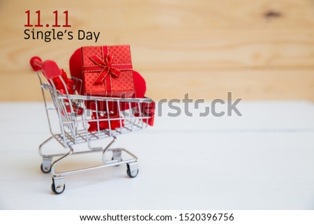 Online shopping of China, 11.11 single's day sale concept. The shopping cart and red heart pillow on white and brown background with copy space for text 11.11 single's day sale.