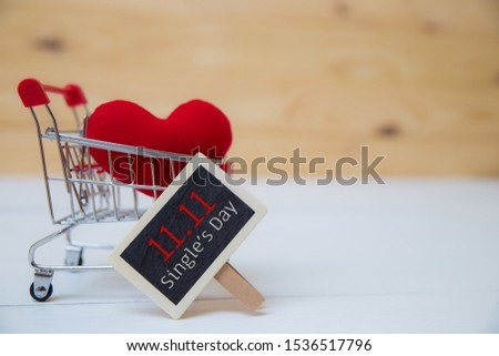 Online shopping of China, 11.11 single's day sale concept. The shopping cart, red ribbon and red heart pillow on white and brown background with copy space for text 11.11 single's day sale.