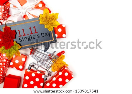 Online shopping of China, 11.11 single's day sale concept. The shopping cart, white ribbon and red gift boxes on white and brown background with copy space for text 11.11 single's day sale.