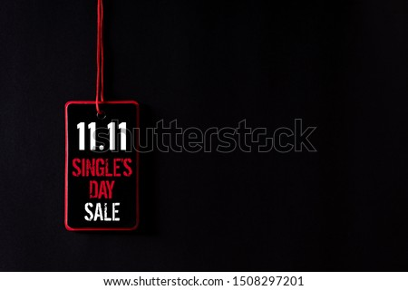 Online shopping of China, 11.11 single's day sale concept. Top view of Black and red paper tag with the text 11.11 single's day sale on a black background.