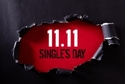 Online shopping of China, 11.11 single's day sale concept. Top view of Black torn paper and the text 11.11 single's day sale on a red background.