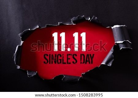 Online shopping of China, 11.11 single's day sale concept. Top view of Black torn paper and the text 11.11 single's day sale on a red background. Foto stock ©