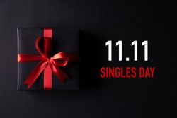 Online shopping of China, 11.11 singles day sale concept. Top view of black christmas boxes with red ribbon on black background with copy space for text 11.11 singles day sale.