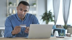 Online Shopping on Laptop by Young African Man