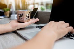 Online shopping - Paper cartons or parcel with a shopping cart logo on a woman hands and laptop keyboard. Shopping service on The online web and offers home delivery.