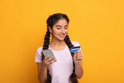 Online Shopping. Portrait of smiling indian woman using her mobile phone and holding debit credit card isolated over yellow studio background. Money Transfer, Digital Instant Payment Concept