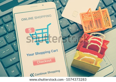 Online shopping / retail ecommerce and delivery service concept : Moblie with shopping app, a credit card on a laptop, depicts consumers purchase or order products from suppliers or digital stores. #1074373283