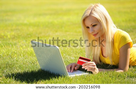 Online Shopping. Smiling Blonde Girl with Laptop using Credit Card and Lying Green Grass.