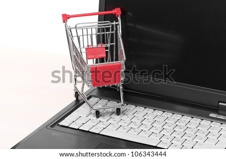 Online shopping. trolley on laptop isolated on white