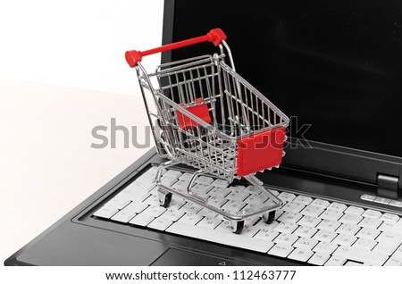 Online shopping. trolley on laptop on white