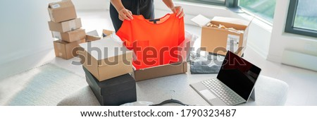 Online store selling clothes on website working on laptop ecommerce business from home. Woman packing new clothing fashion purchase in shipping packages for delivery. Panoramic banner.