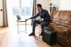 Online studying. A young man is watching video tutorial, video classes how to play guitar, he sits on couch with electric guitar and combo amp near