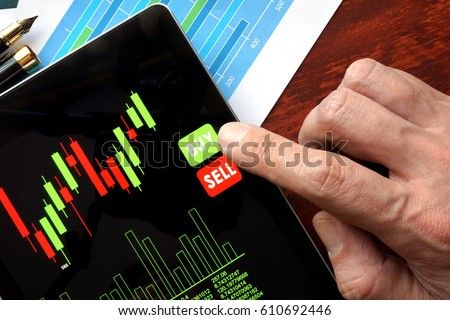 Online trading concept. Tablet with financial stock data and finger.