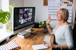 Online training teacher. Day to day new normal office Work from home. Smiling mature woman having video call via laptop in the studio flat office. Daily routine. Business video conferencing.