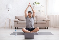 Online training with gadgets. Guy with smart watch doing yoga, watching training video at home in living room in daytime, free space