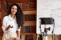 Online Tutoring. Portrait of cheerful woman professor giving virtual class, standing at whiteboard, explaining English language grammar rules and shooting video at camera on tripod