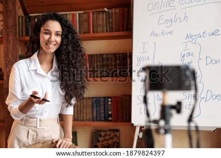 Online Tutoring. Portrait of cheerful woman professor giving virtual class, standing at whiteboard, explaining English language grammar rules and shooting video at camera on tripod ストックフォト ©