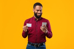 Online Wallet Concept. Smiling black man showing credit card, holding smart phone isolated over yellow studio background wall. Satisfied african american guy shopping, buying via internet