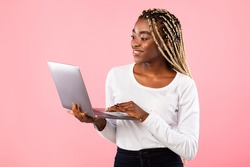 Online Work And Communication. Portrait of smiling black woman holding and using newest laptop computer, standing over pink studio background with copy space. Cheerful female typing on keyboard