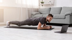 Online workout. Young man doing plank exercise with online tutorial at home, panorama, free space