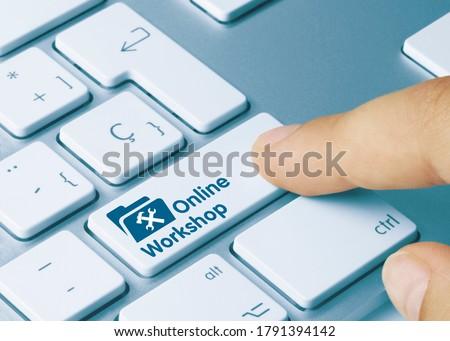Online Workshop Written on Blue Key of Metallic Keyboard. Finger pressing key.