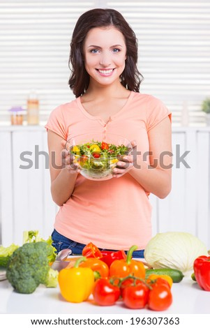 Only healthy food. Beautiful young woman holding a bowl with salad and looking at camera with smile while standing in the kitchen