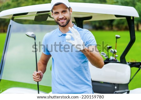 Only the best golf equipment! Handsome young smiling man holding golf ball and driver while standing near the golf cart and on golf course