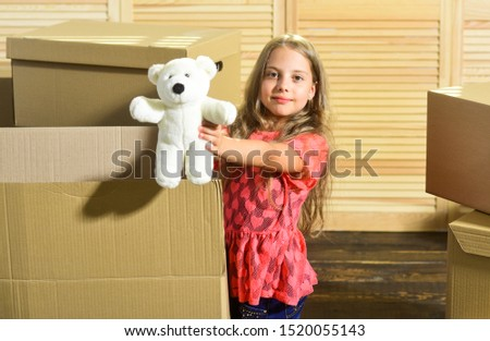 Only true friend. Girl child play with toy near boxes. Move out concept. Prepare for moving. Moving out. Moving routine. Packaging things. Stressful situation. Divorce and separation. Family problem. #1520055143