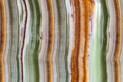 Onyx gemstone texture close up. Green, white, brown and orange stripes. Natural stone mineral background.