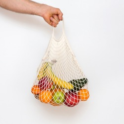 ood delivery for self isolation. Zero waste concept with copy space. Men's hand holding a mesh shopping bags with products. Eco friendly mesh shopper. White background, close up. Plastic free concept.