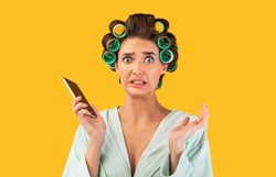 Oops. Embarassed Housewife Holding Mobile Phone Looking At Camera In Confusion Posing On Yellow Studio Background.