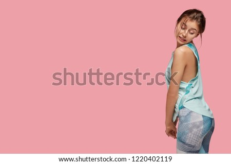 Photo of Oops, I gained some weight! Slim woman turns back, looks at her buttocks, wants to have good result after training, demonstrates sport motivation, poses over pink studio wall with free space on left