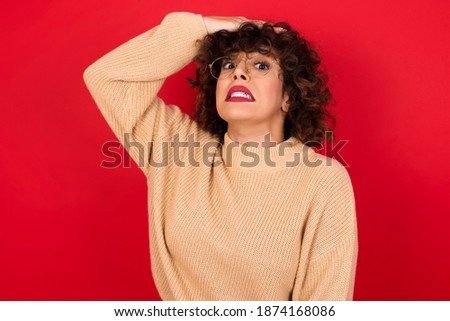 Oops, what did I do? Young beautiful Arab woman wearing knitted sweater standing against red background holding hand on forehead with frightened and regret expression. Foto stock ©