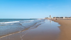Oostende, Belgium - September 13-14, 2020 : The beach of Ostend city. Reflection of the urban skyline in water on the beach.