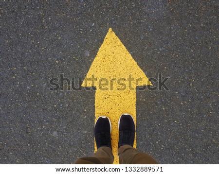 op view of man feet standing over Arrow symbol . Yellow arrow sign at asphalt #1332889571