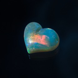Opal jewelry cut, carved into the shape of a heart on a black background.