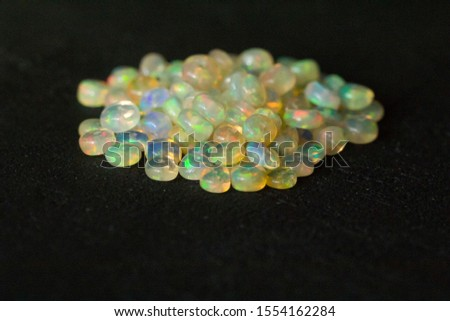 Opals gemstone from Ethiopia lies on black background. White fire opals with rainbowlike fire. Natural fire Ethiopian opal, small stones to create jewelry. Handmade stone jewelry. A pile of stones.