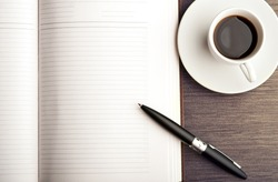 Open a blank white notebook, pen and cup of coffee on the desk
