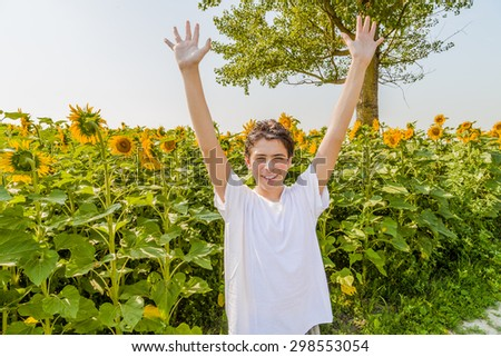 Open air and open arms â?? Caucasian boy is raising his arms in front of yellow sunflower fields during summer in Italian countryside