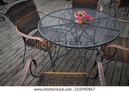 Open-air cafe furniture, wicker chairs and metallic table
