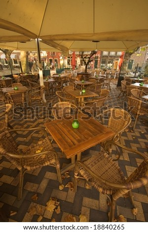 Open air cafeteria with wooden tables and rattan chairs